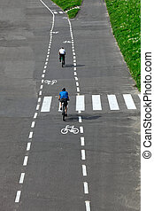 bicyclist riding bicycle on a bike path