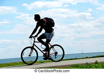Bicyclist - Man riding a bicycle on sea shore trail