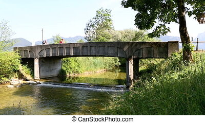Bicyclists cross bridge in summerti - Bicyclists cross a...