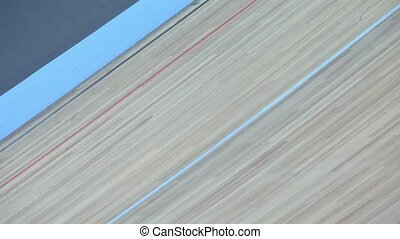 Bicyclists pass by track during race in stadium, view from above