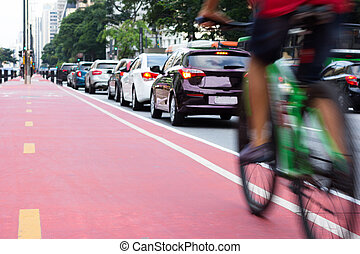 Cyclist passing bicycle lane and while a row of cars are stuck in traffic. Motion blur