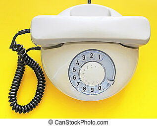 Biege old telephone with rotary dial on yellow background. Flat lay. Top view
