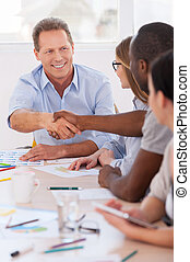 bienvenida, en, board!, grupo de empresarios, sentado, consecutivo, en la mesa, mientras, dos hombres, apretón de manos