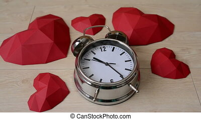 Big alarm clock with red polygonal paper heart shapes