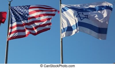 Big American and Israeli flags waving together on a windy...