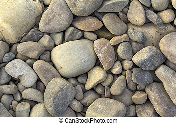 Big and small grey river stones close up background