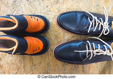 Big and small shoes on wooden background