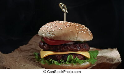 Big appetizing burger with meat cutlet, onion, vegetables, ...