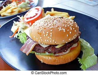 Big appetizing fast food sandwich with lettuce, tomato, smoked h