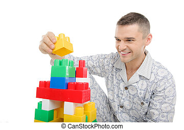 Big baby. Young man in pajamas playing toys while sitting isolated on white