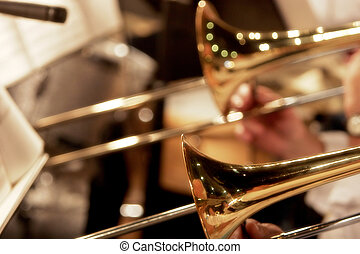 Close up of the trombone section of a big band performance (shallow focus).