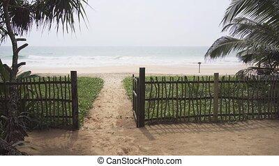 Big beach. View through the fence and the gate. Sri Lanka,...