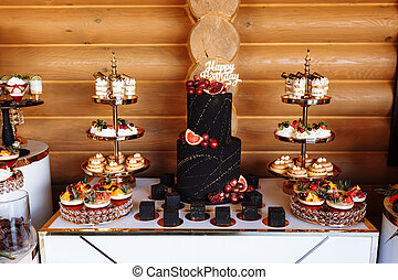 big black birthday cake with fresh fruits and sweets on a festive table. Candy bar. Table with different sweets for party