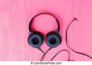Big black headphones on a pink background