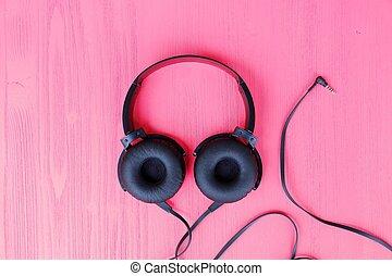 Big black headphones on a pink background