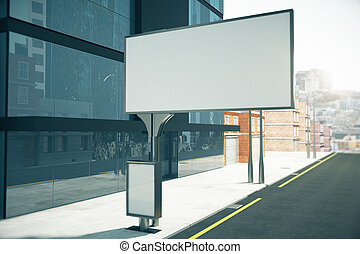 Big blank billboard and small blank poster on city street close to business center, mock up