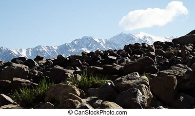 Big blocks of stone in front of snowy mountains - A tilting,...