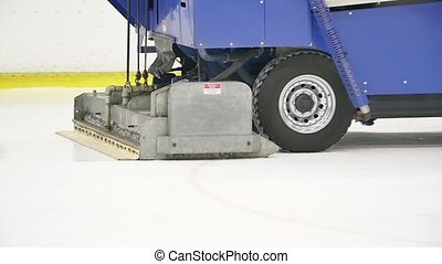 Big blue ice resurfacer truck polishes ice rink