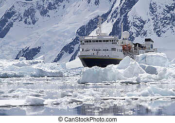 big blue tourist ship in the ice in the background of the Antarc