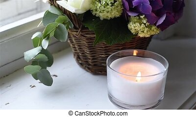 Big bouquet of fresh flowers, purple hydrangeas and white roses in a wicker basket and a candle on a windowsill, interior decoration, vintage style