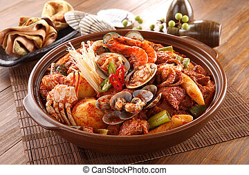 Big bowl of Spicy Seafood galbijjim with clams, shrimp, octopus, crab, potatoes, onion and mushroom on wooden korean table