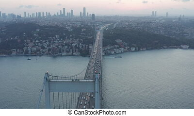 Big Bridge leading into the City Skyline, Car traffic at Sunset in Istanbul, Aerial Dolly Slide left