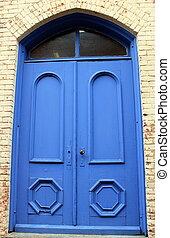 Big bright blue doorsin brick wall