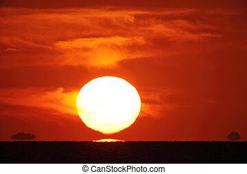 Big bright setting sun - Bright big sun on the sky with...