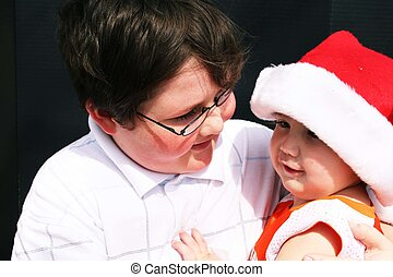 Big brother holding baby with santa hat on