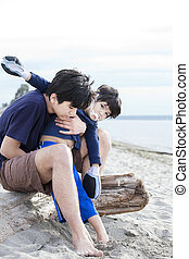 Big brother holding disabled boy on beach