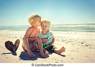 Big Brother Kissing Young Child on Beach - two children, a...