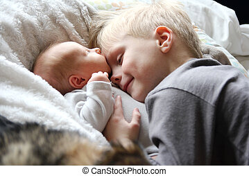 Big Brother Looking at Newborn Baby with Love