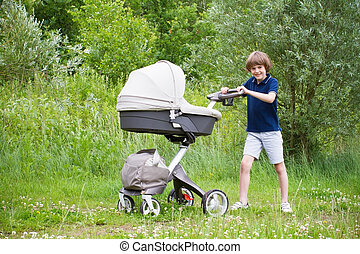 Big brother pushing a stroller in the park