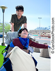 Big brother pushing happy disabled boy in wheelchair