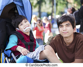 Big brother taking care of disabled little boy in wheelchair outdoors. Child has cerebral palsy.