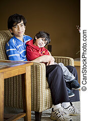 Big brother taking care of disabled sibling with cerebral palsy