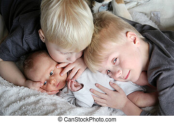 Big Brothers Hugging Newborn Baby Sister