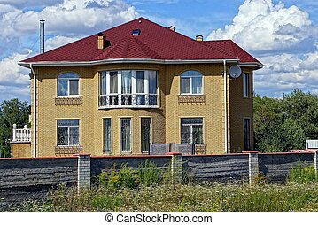 Big brown house under a red tiled roof behind an fence in the grass