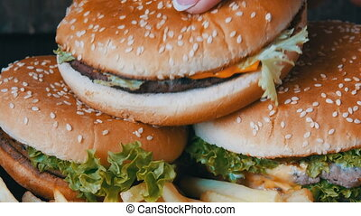 Big burgers close up view. A woman's hand takes a hamburger with a salad leaf and chop inside