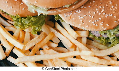 Big burgers on plate next to a french fries - Big burgers on...