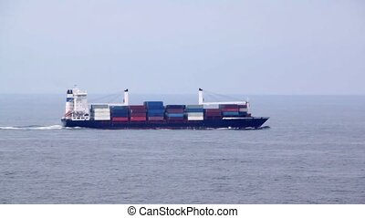 big cargo ship full of containers floats on waves in sea