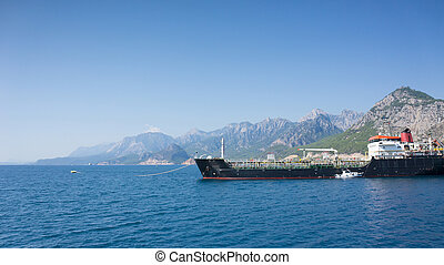 Big cargo ship in Mediterranean Sea, mountains on background