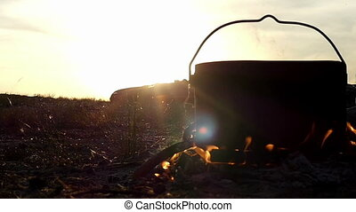 Big cauldron stands in a campfire. It boils hot water at sunset in slow motion
