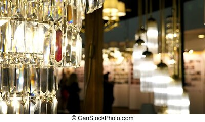 Big chandelier in lights section in store. Lamps for sale.