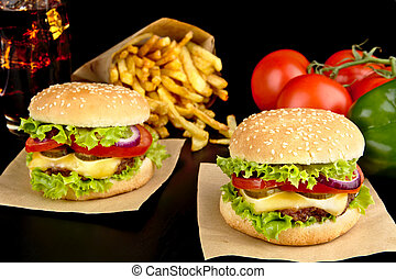 Big cheeseburgers on paper,french fries and glass of cola on black