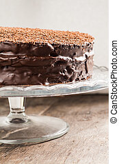 big chocolate cake on festive glass stand