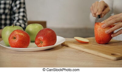 Big close shot of cutting red and yellow apples on accurate...