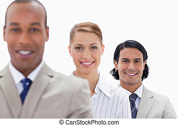 Big close-up of workmates smiling in a single line with focus on the last man