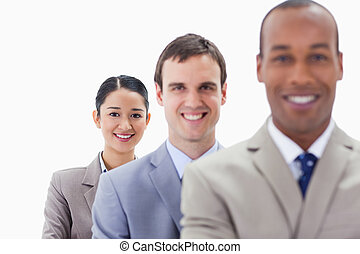 Big close-up of workmates smiling in a single line