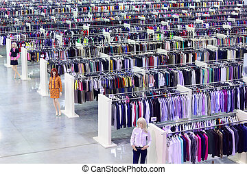 Big clothing store, dummies and many rows with hangers, ...